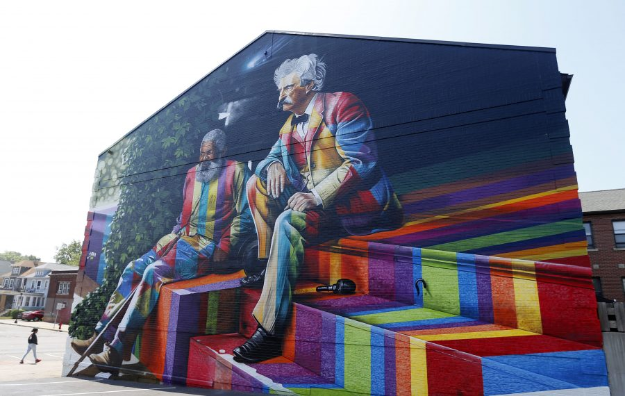 A pedestrian walks past a new mural by Brazilian artist Eduardo Kobra depicting Mark Twain and his friend, John Lewis, on the side of a People Inc. senior housing complex at 1188 Hertel Ave. (Mark Mulville/Buffalo News)