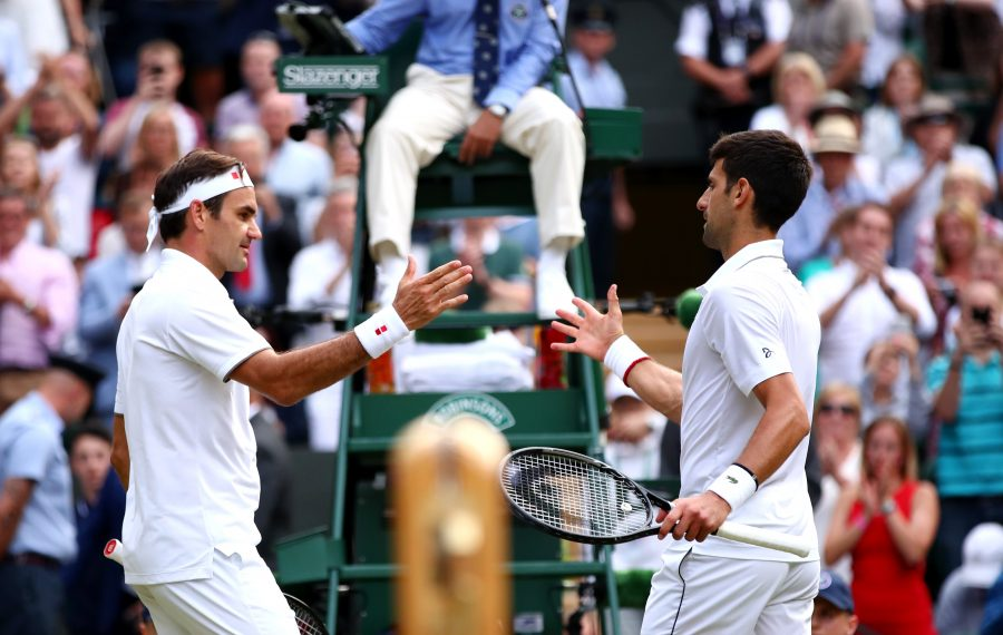Novak Djokovic of Serbia, right, shakes hands with Roger Federer of Switzerland at the net following victory in the men's singles final at the All England Lawn Tennis and Croquet Club on Sunday, July 14, 2019 in London. (Getty Images)
