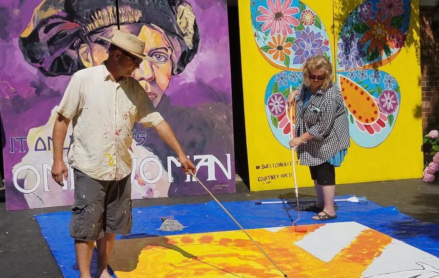 With two of their other works behind them, artists Craig and Elizabeth Thomas work on a Beatles mural for display at Lockport's Sweet Chalk Festival July 10, 2019. (Thomas J. Prohaska/The Buffalo News)