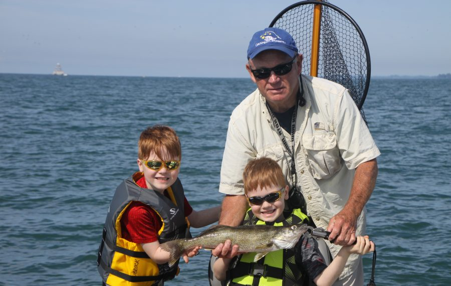 Aiden and Connor Frost of Blasdell show off a walleye with Capt. Ned Librock of Catching Dreams Charters. (Bill Hilts Jr./Buffalo News)