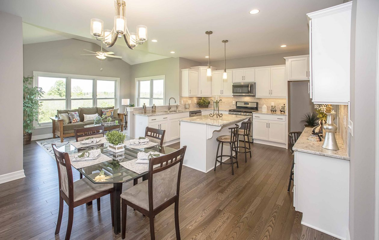 A professional kitchen features a large island with breakfast bar and a nearby, oversized walk-in pantry (not shown).