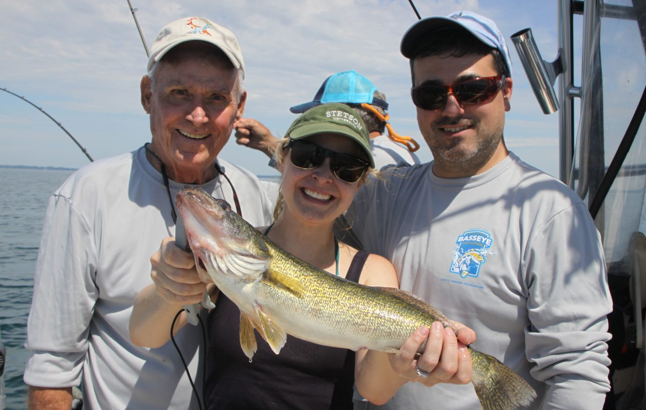 Nicole Ellis of Buffalo shows off a walleye she caught during the BassEye contest last Friday. She is flanked on the left by her Dad, Capt. Gary Ellis, and on her right by her husband Joe Gavigan of Buffalo. (Bill Hilts, Jr. photo)