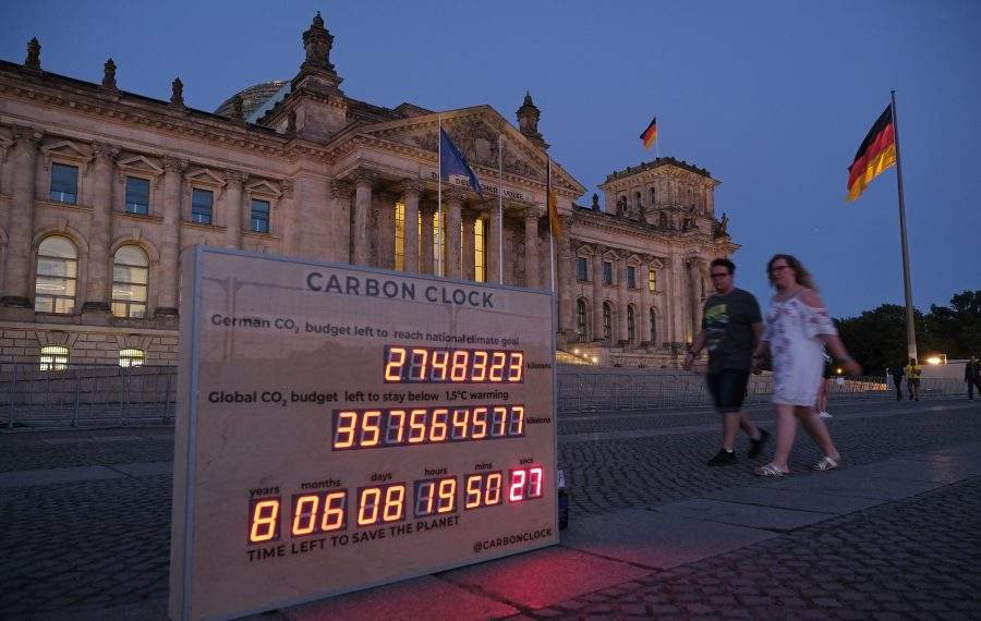 """A couple walks past a """"carbon clock"""" meant as a vigil being held by the climate awareness movement Fridays or Future in front of the Reichstag in Berlin, Germany last month. The clock shows the time remaining before, should the world's carbon emissions continue at the current rate, the globe's average temperature will rise above 1.5 degrees Celsius. (Photo by Sean Gallup/Getty Images)"""