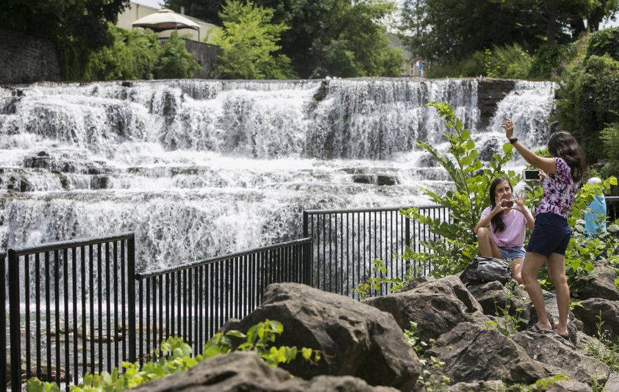Meg Syracuse takes photos for her daughter Justine in front of Glen Falls, which is near the site of the Glen Park Art Festival. (Shuran Huang/News file photo)