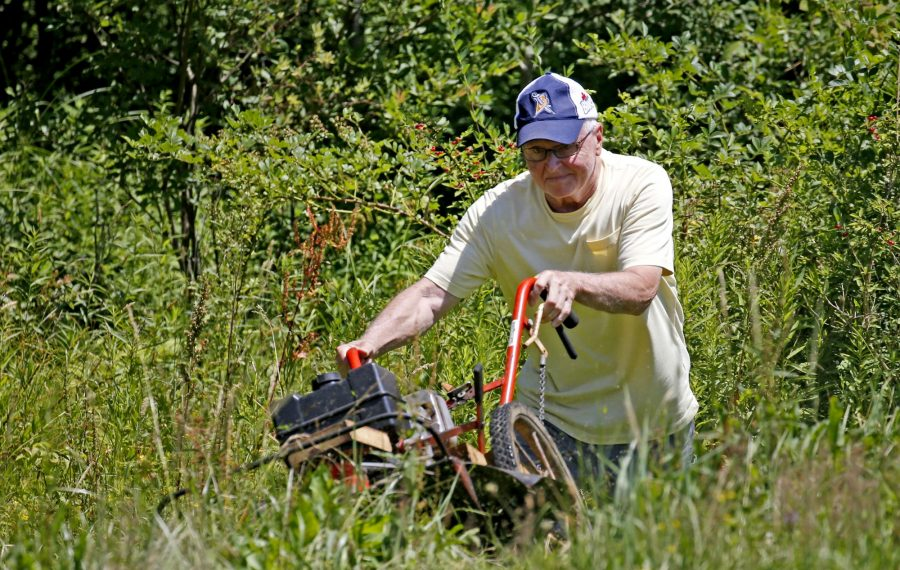 Bob Shanahan, 82, uses his  Bush Hog gas machine to clear brush on his Arcade property. He says he used to get winded just walking to the mailbox before undergoing transcatheter aortic valve replacement surgery in February. (Robert Kirkham/Buffalo News)