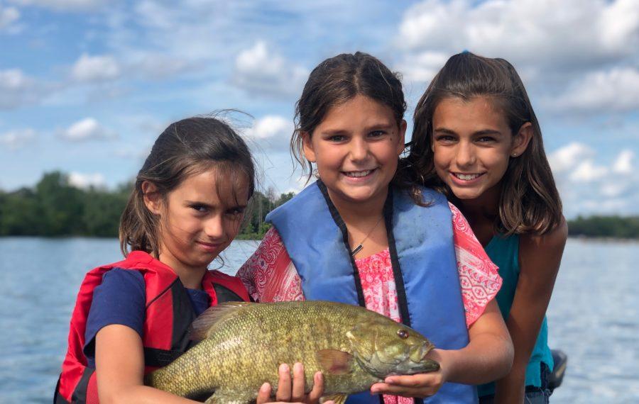 Charlotte Shea of Tonawanda, Lucy Carlisi and Carmella Carlisi of Flagler Beach, Florida caught this smallmouth bass in the Upper Niagara River using a Ned Rig while fishing with Capt. Ryan Shea of Brookdog Fishing. (Photo by Ryan Shea)