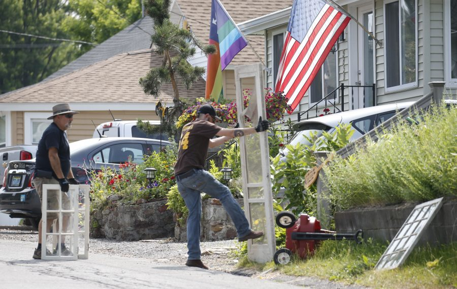 """An assistant kicks in the screen of a porch door to add to the realism on the set of """"A Quiet Place 2"""" during filming in July in Olcott. (Robert Kirkham/News file photo)"""