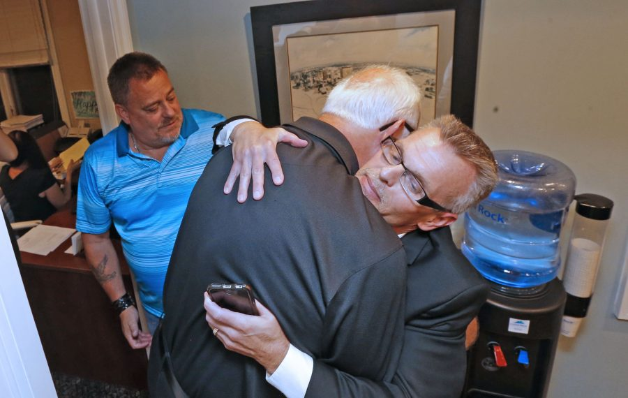 Michael Whalen, center, looks on as fellow sex abuse survivors Gary Astridge, left, and Kevin Koscielniak embrace after filing lawsuits in the Child Victims Act just after midnight at the law offices of Steve Boyd at 40 N. Forest Road in Amherst. (Robert Kirkham/Buffalo News)