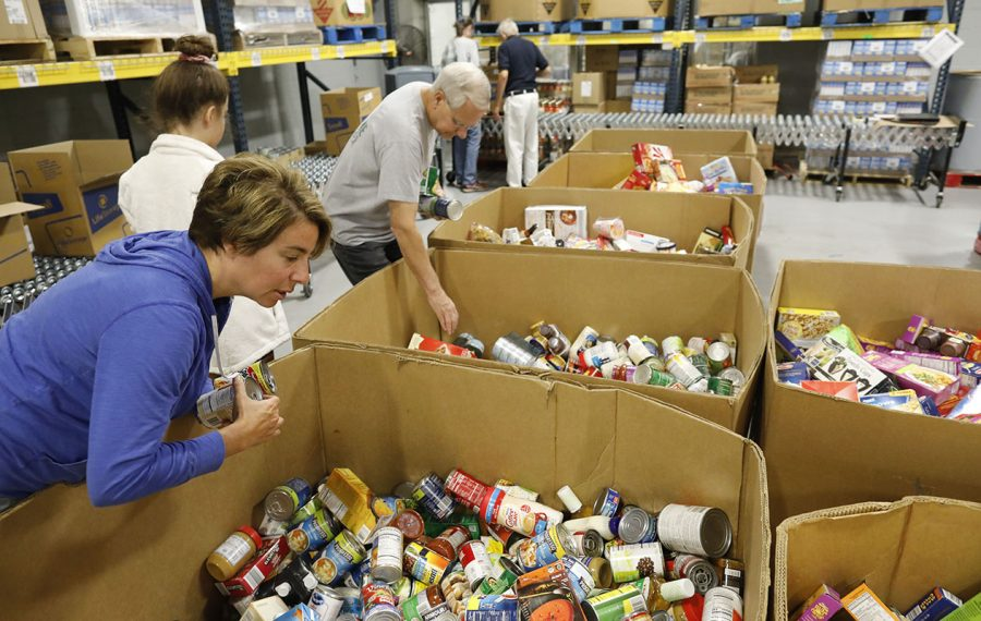 Volunteers sort boxes of donated food to pack up for delivery to local food pantries at the FeedMore WNY food bank distribution center. (Derek Gee/Buffalo News)