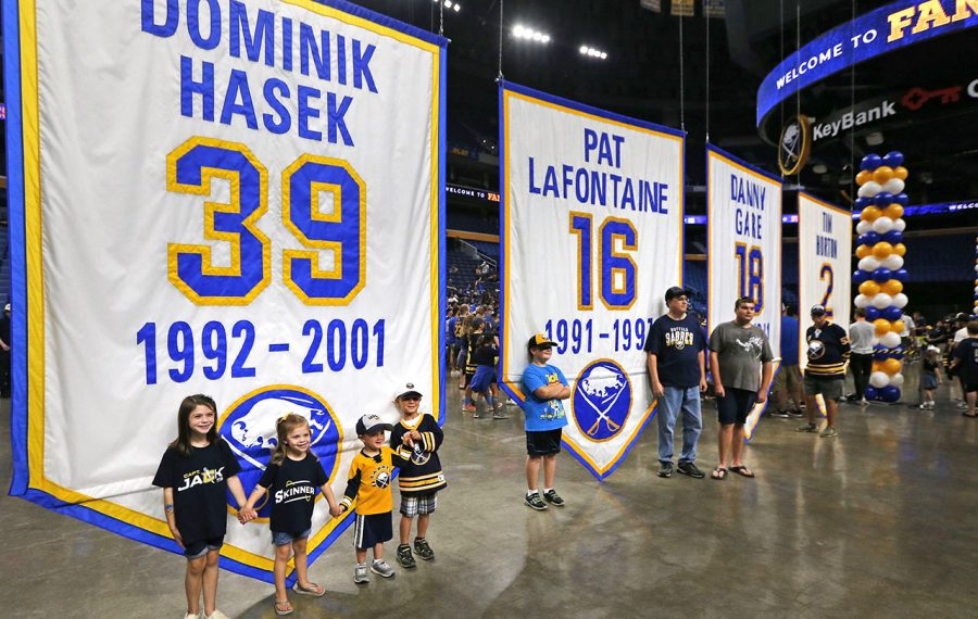 Fans pose with the rafter banners that were lowered for Saturday's event. (Robert Kirkham/Buffalo News)