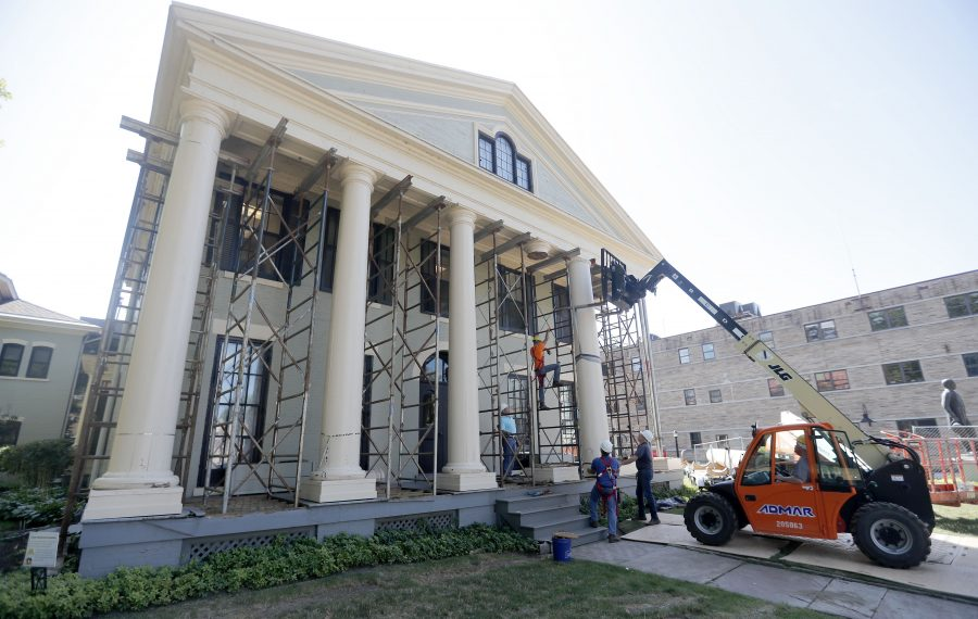 Crews from Northwood Historic Restoration remove the wooden columns on the porch of the Theodore Roosevelt Inaugural Site on Delaware Avenue. (Mark Mulville/Buffalo News)