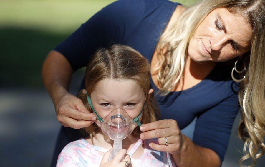 Lindsay McMichael, right, works with her daughter, Delaney Reil, 5, on the right way to put on a nebulizer.  The Pendleton mother and daughter both have asthma, which can act up at the start of the school year. (Mark Mulville/Buffalo News)