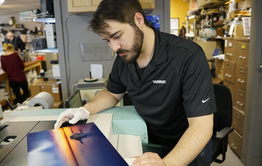 Benjamin Searle checks a print as it comes out of the inkjet printer at Delaware Camera in Buffalo. (Derek Gee/Buffalo News)
