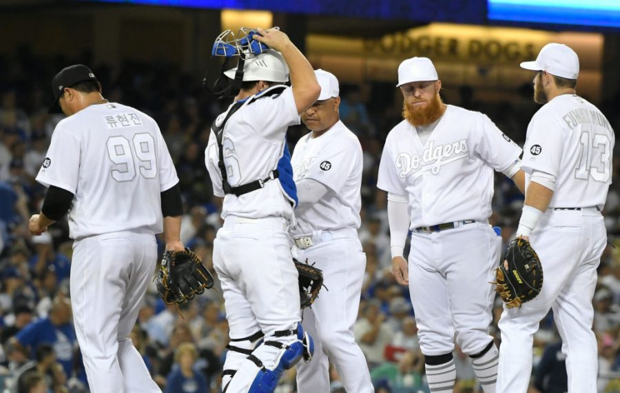 Wearing their all-white Players Weekend jerseys, Dodgers manager Dave Roberts runs a meeting on the mound Friday night after removing pitcher Hyun-Jin Ryu from their series-opening loss to the Yankees. (Getty Images)