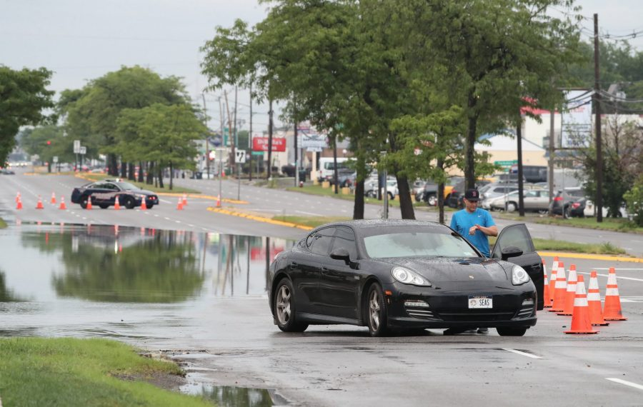 A car was stranded in the middle of Niagara Falls Boulevard near Romney Road because of excessive water and flooding. (James P. McCoy/Buffalo News)