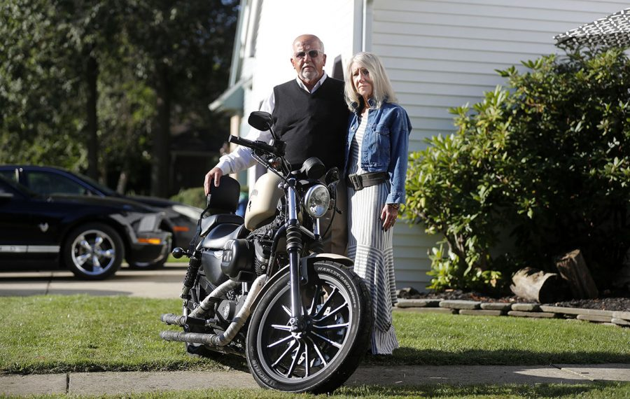 """Sigmund and Barbara Szymanski stand by their son Daniel """"DJ"""" Szymanski's motorcycle. DJ Szymanski was murdered five years ago at the hands of his fellow Kingsmen.   (Mark Mulville/Buffalo News)"""