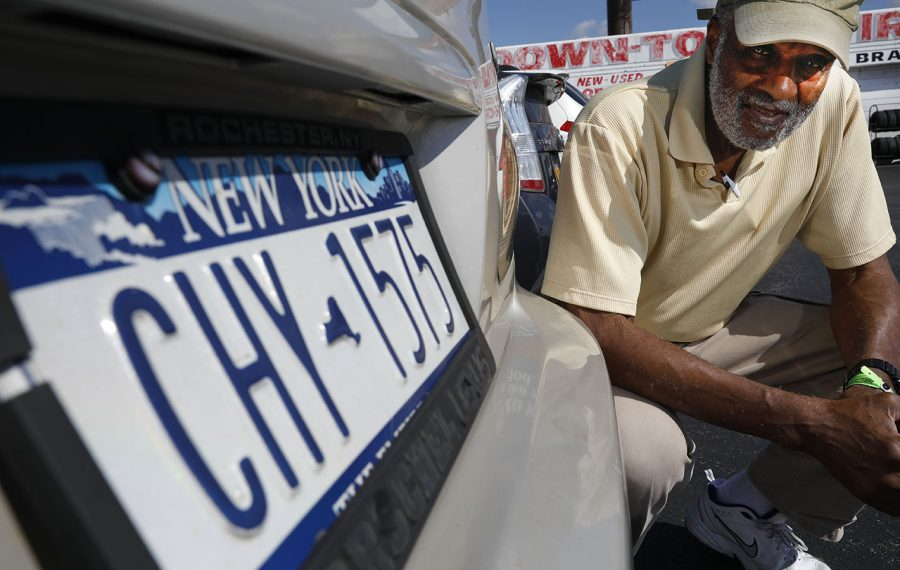 Theodore Kirkland crouches down at the rear of his late wife, Winona's car, which still has the older style license plates on it, which are in mint condition, Friday, Sept. 6, 2019. (Derek Gee/Buffalo News)