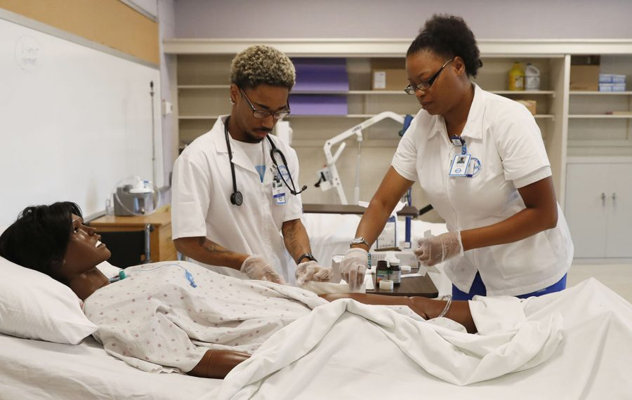 Kenadee Noble, left, and Maria Jones, students in an Erie I BOCES licensed practical nursing program, practice wound care on a mannequin at the new Gerard Place Community Center, which offers job training and other services.  (Sharon Cantillon/Buffalo News)