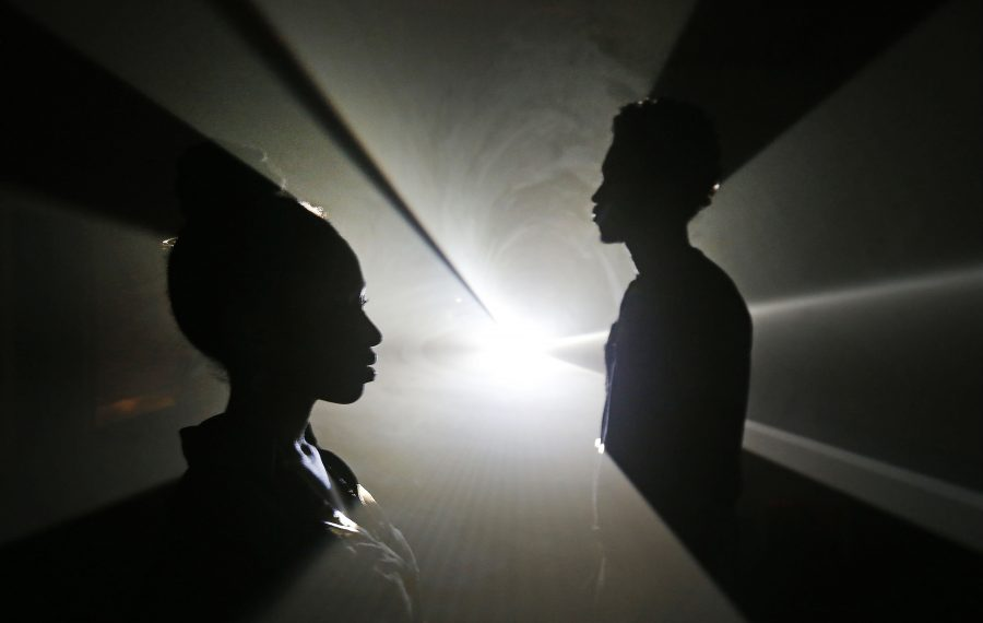 Alex Miller, left, and Blessing Ese explore one of the projected pieces featured in the light installation by the British artist Anthony McCall, which serves as the last major exhibition at the Albright-Knox Art Gallery before it closes in November.  (Robert Kirkham/Buffalo News)