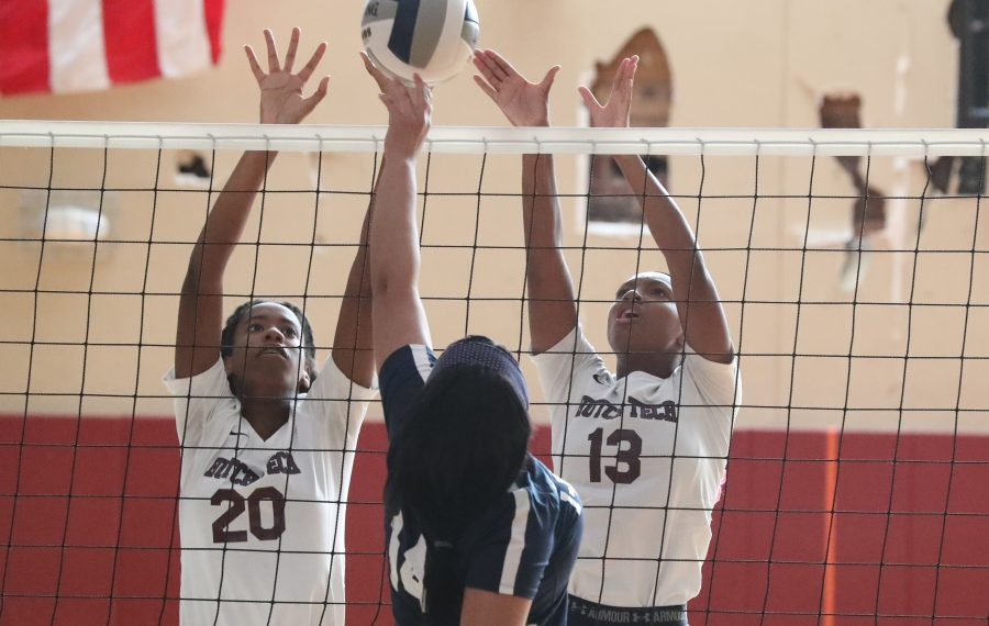Middle blocker Desha Renshaw and Tatiana Boyd of Hutch-Tech block the ball past I-Prep/Grover's Taylor Rizzo in the first set of their girls volleyball match Thursday (James P. McCoy/Buffalo News)