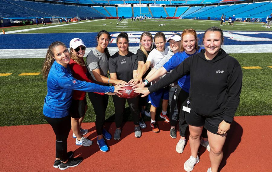 Pictured at New Era Field, from left to right, are: Alessandra Santorelli, equipment intern  Ashley Cohrs, football operations intern; Andrea Gosper, scouting intern; Mackenzie Marques, athletic training intern; Devin Worthington, athletic training intern; Jo Clubb, applied sports scientist; Christine Dziedzic, dietician; Kelly Bray, seasonal athletic training intern; Audrey Yokopovich, seasonal athletic training intern. (James P. McCoy/Buffalo News)