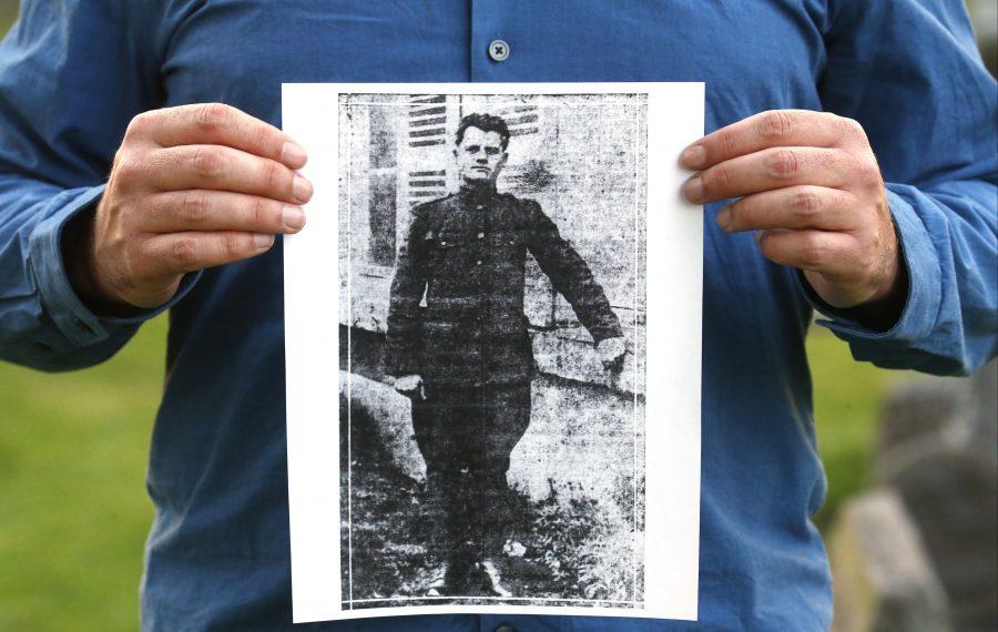 Chris Hawley at Holy Cross Cemetery, with an image of Casimer Mazurek. (Robert Kirkham/Buffalo News)