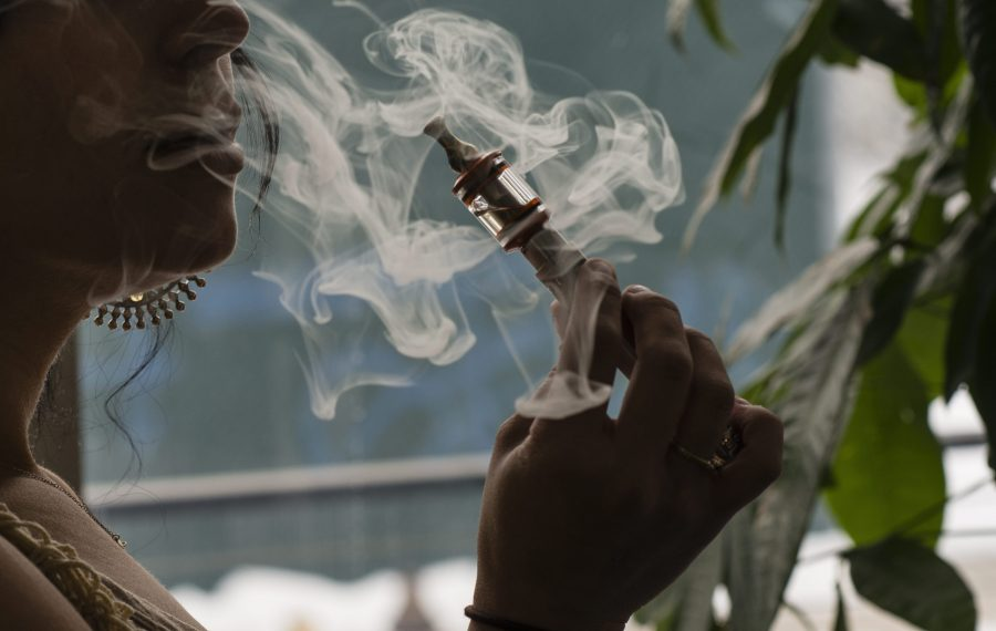 Ilona Orshansky, owner of Brooklyn Vaper, uses an e-cigarette, in her shop in Brooklyn. The state Health Department has noted 41 cases of vaping-related illnesses across New York.(Bloomberg News file photo)