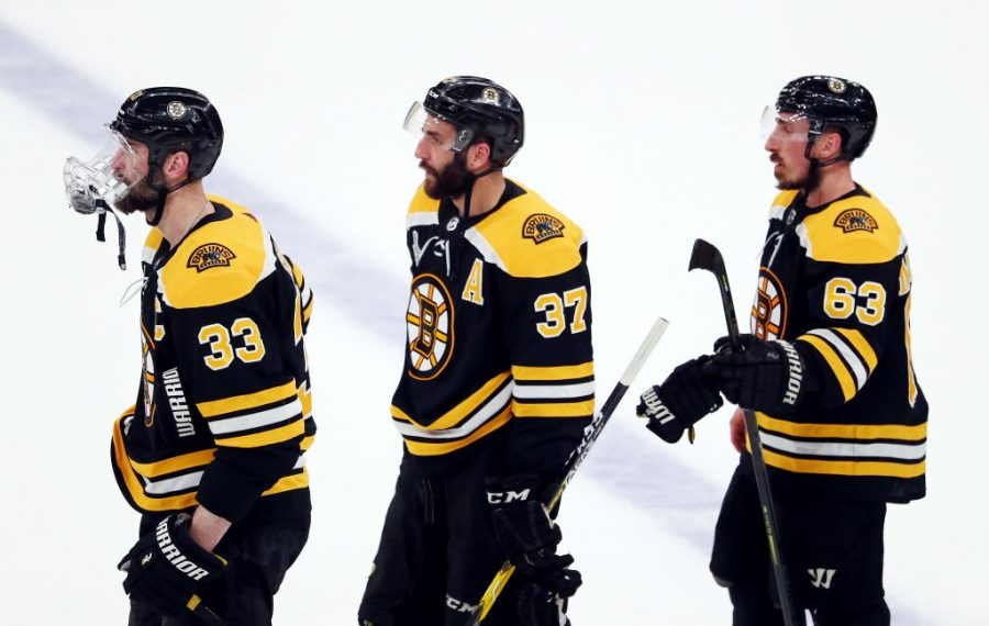 From left, Zdeno Chara, Patrice Bergeron and Brad Marchand can only watch as the St. Louis Blues celebrate at the final buzzer of Game 7 of the Stanley Cup final. (Getty Images)