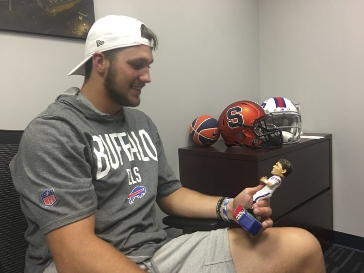 Josh Allen, in the Buffalo Bills' administrative offices. sees one of his new bobblehead dolls for the first time. (Tim O'Shei/Buffalo News)