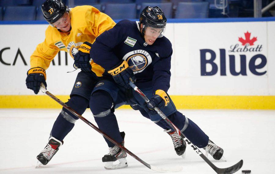 Buffalo Sabres defenseman John Gilmour (58) skates away from forward Casey Mittelstadt (37) during training camp at KeyBank Center.  (Derek Gee/Buffalo News)