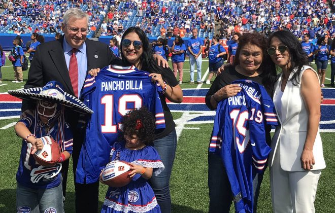 """The family of Ezra """"Pancho Billa"""" Castro took part in a pregame ceremony Sunday with Bills owners Terry and Kim Pegula. (James P. McCoy/Buffalo News)"""