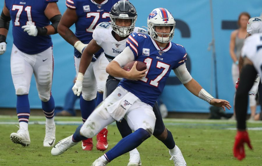 Bills quarterback Josh Allen rushes for a first down over Titans outside linebacker Kamalei Correa in the fourth quarter (James P. McCoy/Buffalo News)