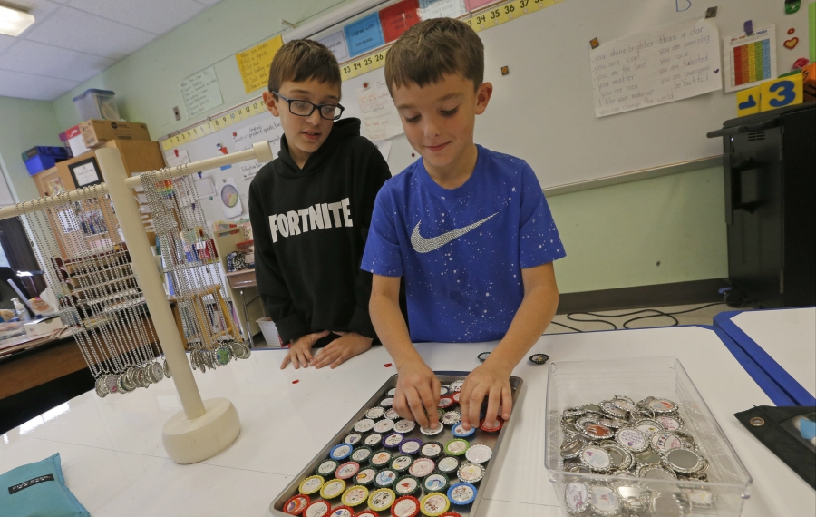 Fitth-graders Nicholas Guzzetta, left, and Kurran O'Connor, both 10, check inventory of the message bottle caps before warehousing them at J.T. Waugh Elementary School  in Angola. (Robert Kirkham/Buffalo News)