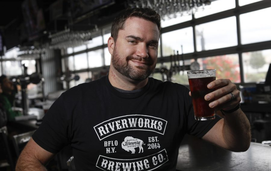 Chris Herr, head brewer for the Pearl Street Brewery family of breweries, lifts a pint of his new Raisin Bran-themed beer, the latest in a line of cereal-inspired brews. (Derek Gee/Buffalo News)