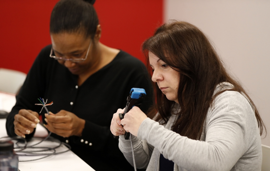 Jessica Rogers, right, and Tina Hatchett, left, make a network cable in an Intro to Networking class at Trocaire College's new Technology Center. (Mark Mulville/Buffalo News)