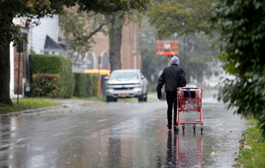 A person walks with a shopping cart in the rain on Doat Street on the Cheektowaga/Buffalo border Wednesday, October 16, 2019.  The state Department of Health announced a series of public meetings to discuss regional cancer studies.                (Mark Mulville/Buffalo News)