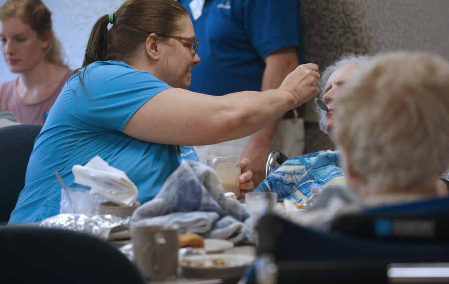 Certified nursing assistant Carolyn Delzer feeds a resident at Absolut Center for Nursing and Rehab at Aurora Park, a nursing home in East Aurora.  (Robert Kirkham/News file photo)