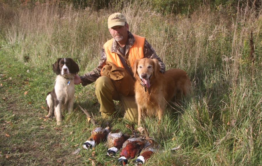 Joel Spring of Ransomville displays four birds after a successful day at Wilson-Tuscarora State Park of hunting with Bill Hilts Jr. as Fred (left) and Max look on. (Bill Hilts Jr./Buffalo News)