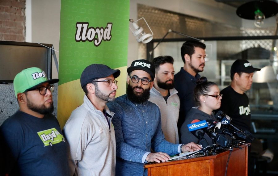 Lloyd owners Pete Cimino, in blue shirt, and Chris Dorsaneo, in blue hat and light gray pullover, speak with reporters about the social media controversy that erupted last week after a Lloyd truck served lunch at the federal immigration detention facility in Batavia. (Mark Mulville/Buffalo News)