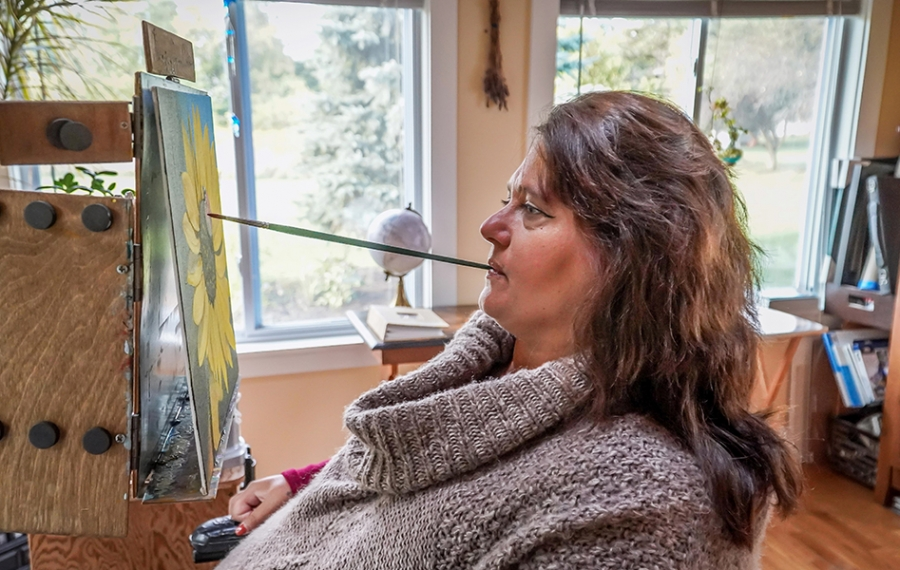 Artist Nancy Hall painting in her East Aurora home studio. (Alicia Wittman)