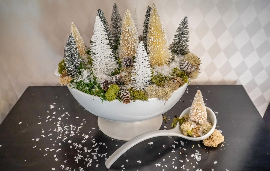 Evoking the calm of a wintery woods, a soup tureen showcases a mini-forest of Dollar Store bottle brush trees tucked amongst a bed of natural moss. A dusting of faux snow enhances the serene hyggeligt-inspired display. (Alicia Wittman)
