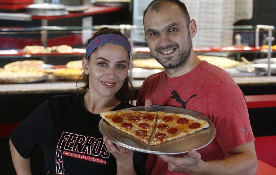 Owners Vali Spahiu and wife Aferdite, left, with two slices of cheese and pepperoni pizza at Ferro's Famous NY Pizza at 3521 Seneca St. in West Seneca. (Robert Kirkham/Buffalo News)