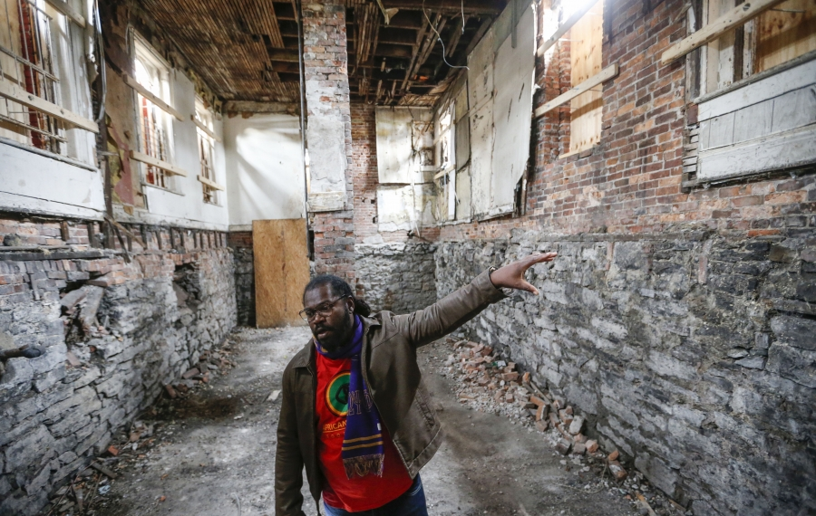 """Alexander Wright points out some of the windows that have been boarded up to stabilize the Carlton Street building his African Heritage Food Co-Op  is converting into a store.  The co-op is a key component in the collaborative effort to build a """"new food economy"""" in Buffalo. (Derek Gee/Buffalo News)"""