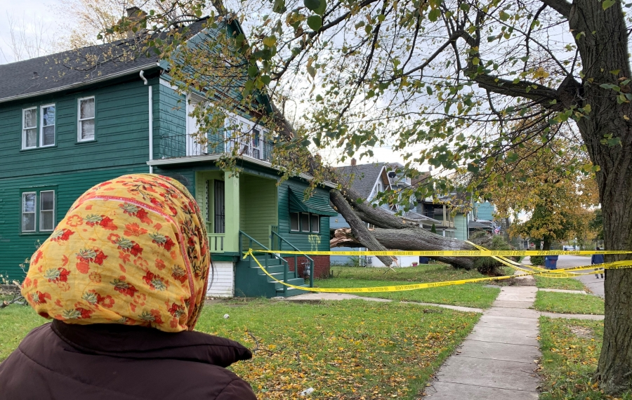 Monowar Begum, a mother of two, looks Saturday at the house she fled from overnight Thursday when a giant tree fell on the roof during a powerful windstorm. (Maki Becker/Buffalo News)