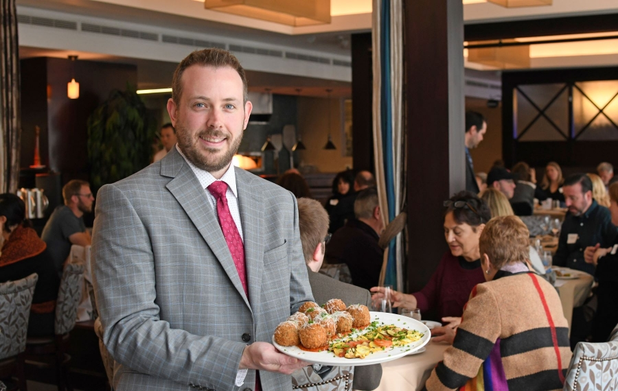 NFCI Hospitality Instructor Daniel DiPirro presents a plate of arancini featured on the seasonal menu at Savor. (Photo courtesy of Niagara Falls Culinary Institute)