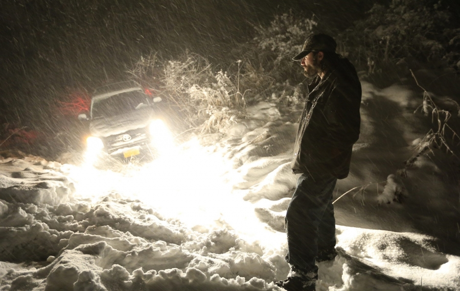 Forecasts called for three feet of snow, but double lake-effect blasts would deliver 7 feet in the hardest-hit areas. Plows could not keep up as the storm rolled in Monday night, Nov. 17, 2014. Here John Dowl waits for roadside assistance after going off Route 219 that night. (Harry Scull Jr./Buffalo News file photo)