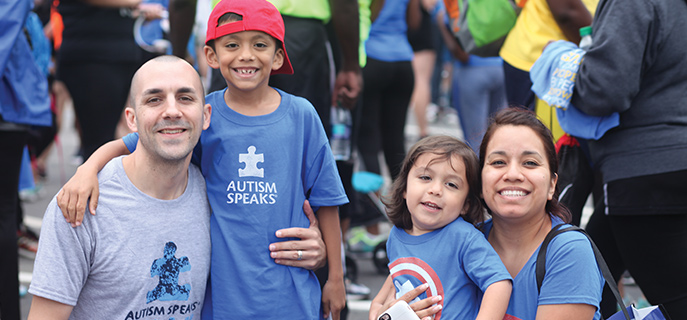 Family of four posing for a picture at an Autism Speaks walk.