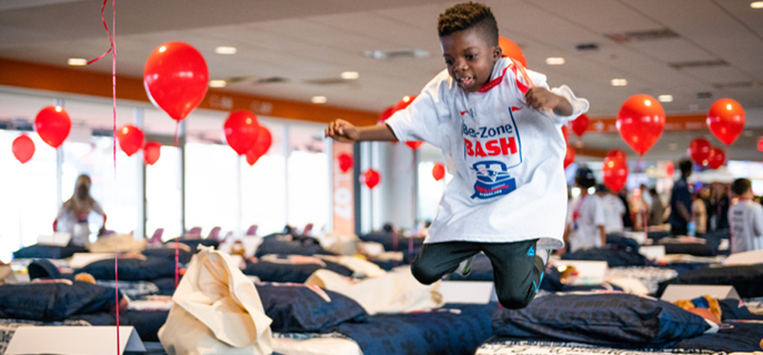 Child jumping on a bed that he just received thanks to the New England Patriots and Mass Coalition's donation of 200 beds to children in need.