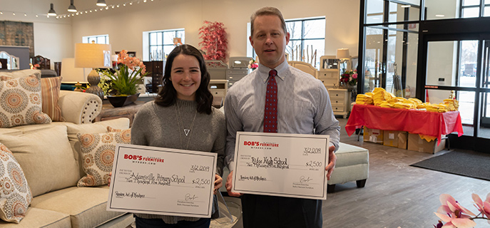 Principal and Pre-K teacher accept Random Acts of Kindness checks for their schools at the grand opening of the Bridgewater, New Jersey Bobs Discount Furniture store.