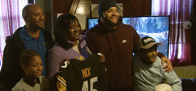 Family posing for a picture after receiving furniture from the Pittsburgh Steelers and Bob's Discount Furniture